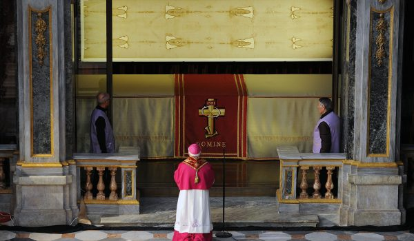 Archbishop of Turin Cesare Nosiglia, center, kneels in front of the Shroud of Turin that went on display for a special TV appearance Saturday, March 30, 2013. The Shroud went on display amid new research disputing claims it's a medieval fake and purporting to date the linen some say was Jesus' burial cloth to around the time of his death. Pope Francis sent a special video message to the event in Turin's cathedral, but made no claim that the image on the shroud of a man with wounds similar to those suffered by Christ was really that of Jesus. He called the cloth an